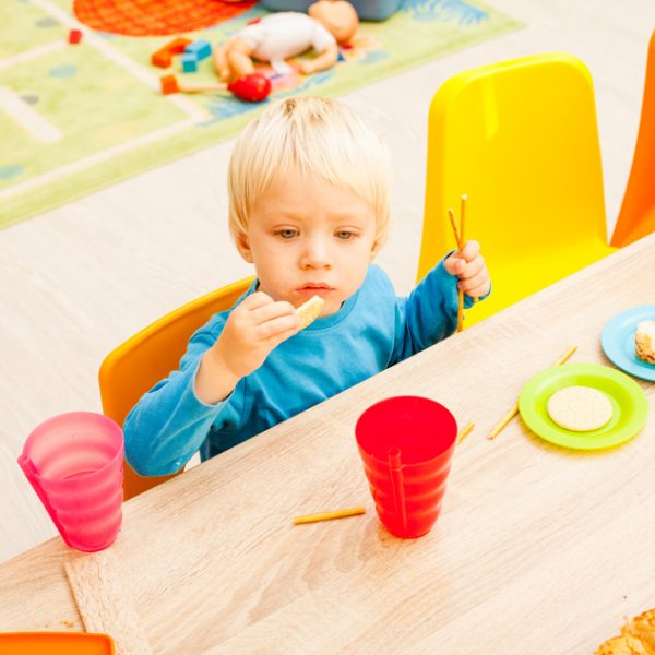 Children are sitting at the table with lunch and eating fruits and cakes